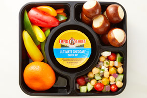 Bento box with cheese dip cup, salad, orange, peppers, soft pretzels
