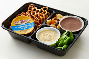 Bento box with cheese dip cup, pretzels, hummus, peas, dried fruit and chocolate pudding