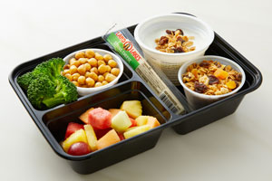 Bento box with cheese stick, fruit, broccoli, chick peas and yogurt with granola