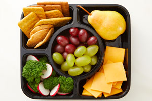 Bento box with cracker cuts, crackers, grapes, pear and vegetables