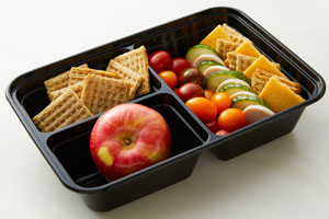 Bento box with cracker cuts, crackers, apple, tomatoes, cucumbers, turkey