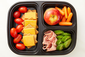 Bento Box with cracker cuts, tomatoes, apple, carrots, cucumber and ham