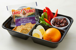 Bento box with cheese cubes, crackers, egg, orange, peppers and raisins
