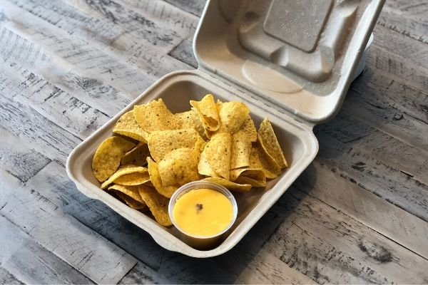 Land O'Lakes Foodservice Aloha Queso Dip with chips in a to-go container