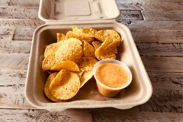 Land O'Lakes Foodservice Chipotle Queso with Corn Chips served in a to-go container