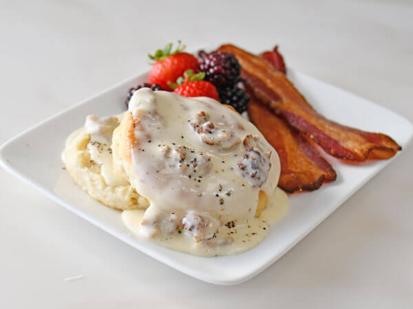 A plate of sausage gravy with biscuits and bacon
