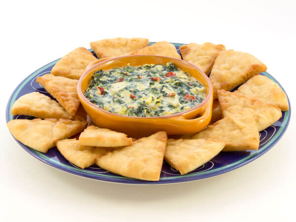 Bowl of spinach artichoke dip with pita bread pieces