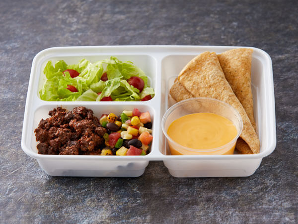 ALT TEXT: Land O'Lakes Foodservice | Mucho Queso Burrito Kit with beef crumbles; corn, black bean and onion salsa; Land O Lakes® Mucho Queso™ Jalapeno Cheese Sauce; flour tortillas; and a side salad
