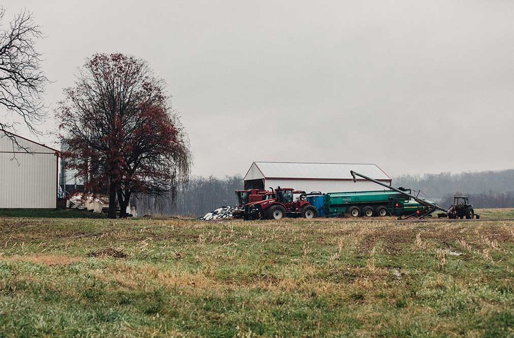 A View Of Sheds On A Farm With Machinery Nearby