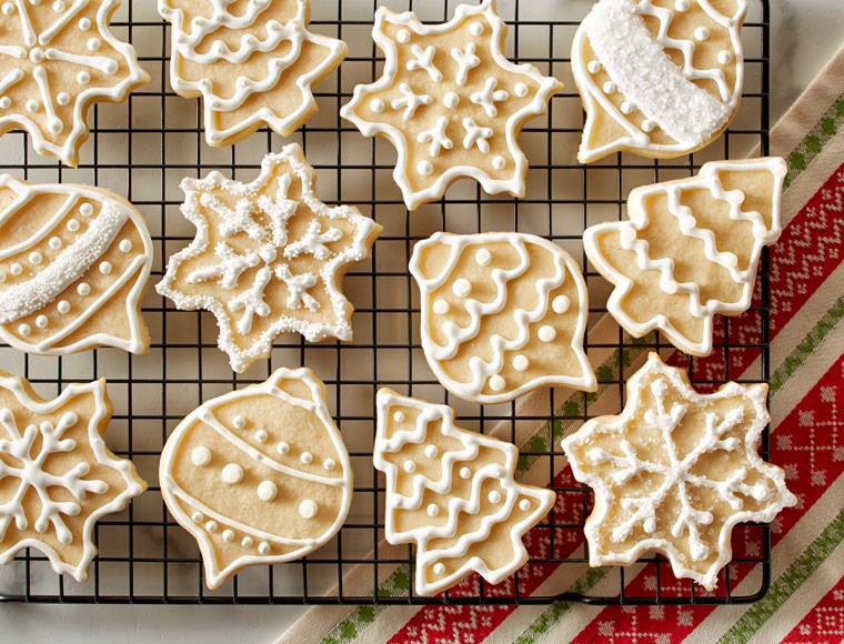 frosted christmas sugar cookies on cooling rack