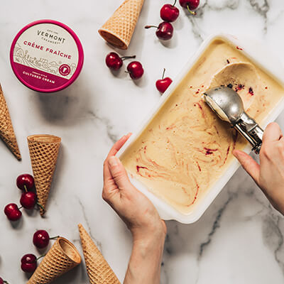 Scooping honey creme fraiche ice cream with cherries and ice cream cones.