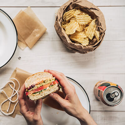 Person holding vegetable sandwich with chips and a soda can.